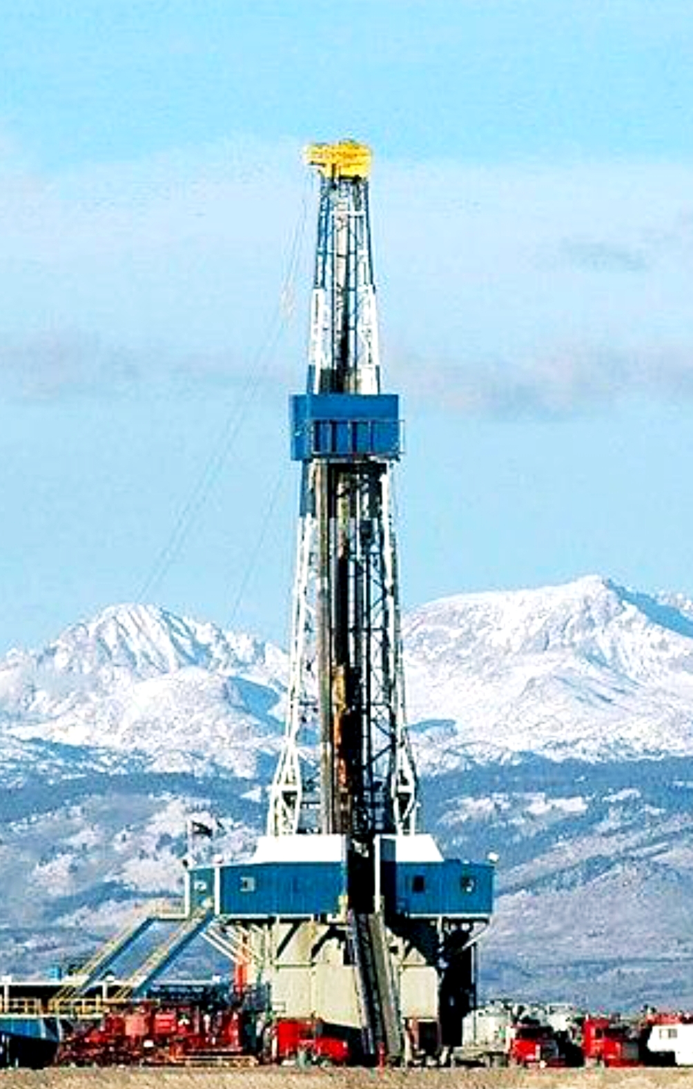 Oil Rig Drilling With Mountains In The Background